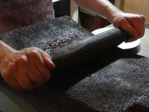 On écrase les fèves de cacao sur un support en pierre volcanique