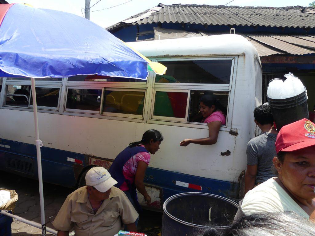 le bus passe en plein milieu du marché, les stands s'écartent et les passagers achètent par la fenêtre
