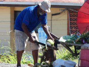 En face du poste de douane, un costaricain tranche des noix de coco à la machete !